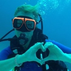 Scuba Diver with gear, hands making heart sign